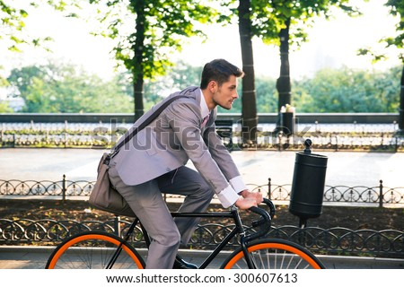 Businessman riding bicycle to work in city park - stock photo