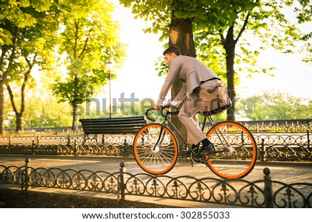 Businessman riding bicycle to work in park - stock photo