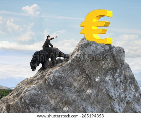Businessman riding black bear pursuing gold euro symbol on mountain peak with sunlight clouds background. Fight back bearish market concept. - stock photo