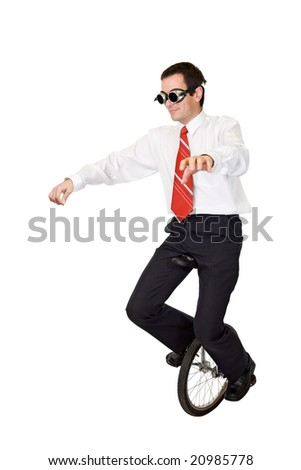 Businessman riding on mono-cycle - concept for reckless business and risk taking - isolated - stock photo