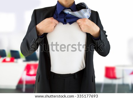 businessman ripping open his shirt and exposing a costume underneath - stock photo