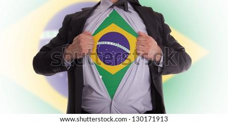 Businessman rips open his shirt to show his Brazilian flag t-shirt - stock photo