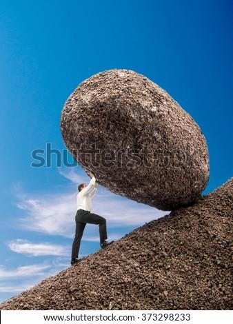 Businessman rolling up giant boulder on slope over blue sky - stock photo