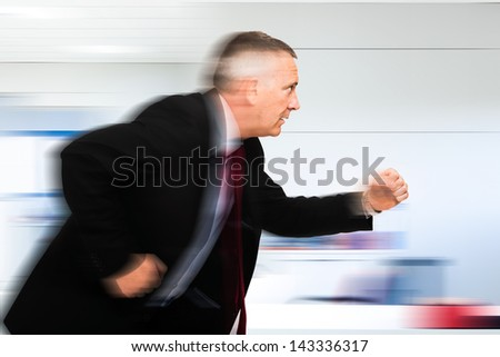 Businessman running in his office - stock photo