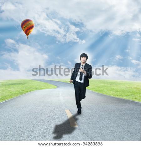 Businessman running on road - stock photo