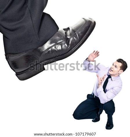 Businessman's foot stepping on tiny businessman - unequal competition concept - stock photo