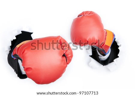 Businessman's hand breaking through a paper wall wearing boxing gloves - stock photo