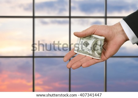 Businessman's hand holding cash. American dollars on sunset background. Papers that change life. Manager's salary bonus. - stock photo