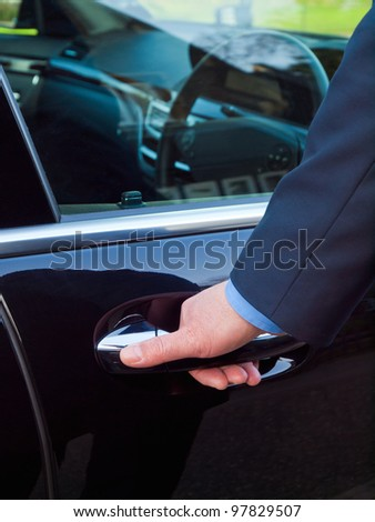 Businessman's hand opening door of his luxury car - stock photo