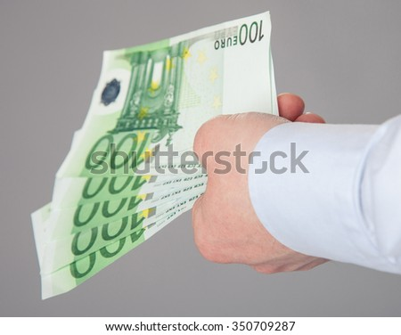 Businessman's hand reaching out euro banknotes - stock photo