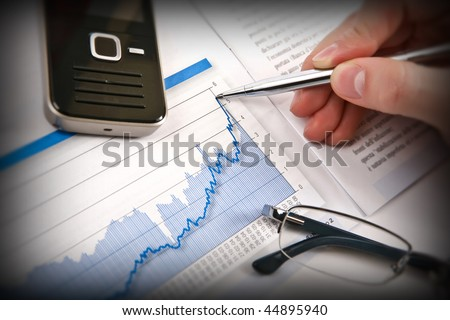 Businessman's hand showing diagram on financial report with pen. Business background 03 - stock photo