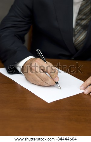 Businessman's hand writing on white sheets - stock photo