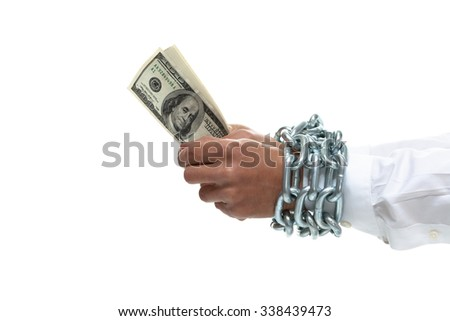 Businessman's hands chained holding money - stock photo
