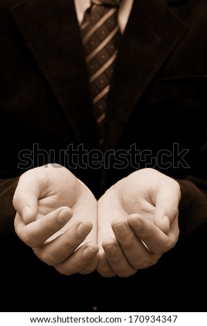 Businessman's hands holding or asking for something. Focus on fingers - stock photo