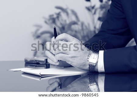 Businessman's hands on the table blue toned - stock photo