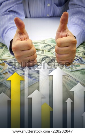 Businessman's hands with thumbs up over bulk of money with arrows pointing upwards showing financial growth - Financial success concept - stock photo