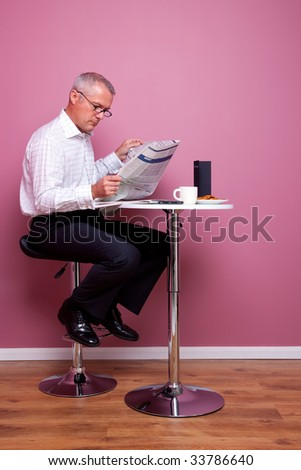 Businessman sat in a cafe reading the morning news, the newspaper has had any copyright issues removed and the text is unreadable. The menu is blank also. - stock photo