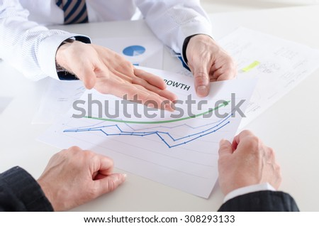 Businessman satisfied with the results showing a financial graph - stock photo