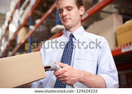Businessman Scanning Package In Warehouse - stock photo