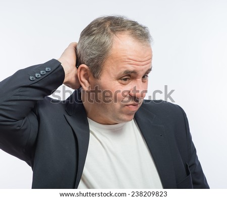 businessman scratches his head - stock photo
