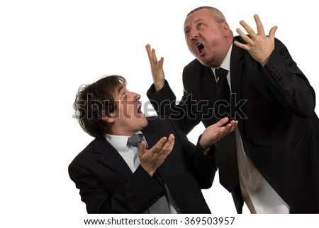 Businessman screaming and fighting at a young colleague. - stock photo