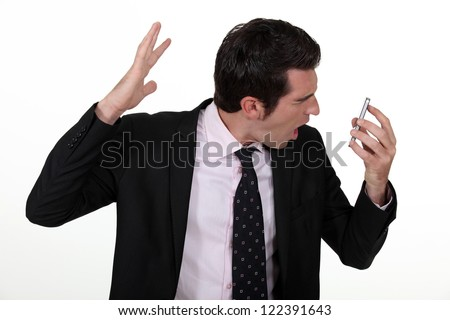 Businessman screaming down the phone - stock photo