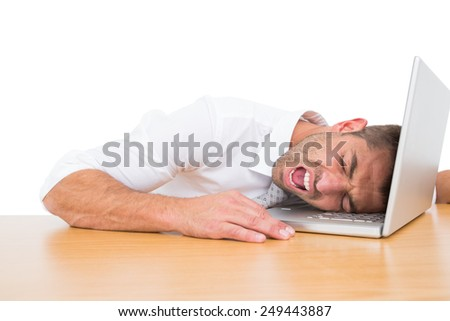 Businessman screaming put his head on laptop on white background - stock photo
