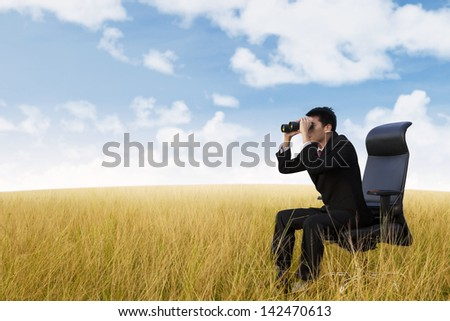 Businessman see vision using binoculars on wheat field - stock photo