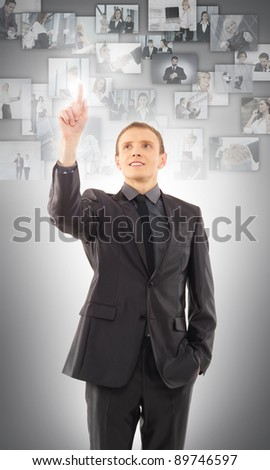 Businessman selecting one picture from the virtual display - stock photo