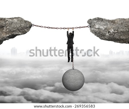 Businessman shackled by heavy concrete ball hanging on iron chains connected two cliffs with cloudy cityscape background - stock photo