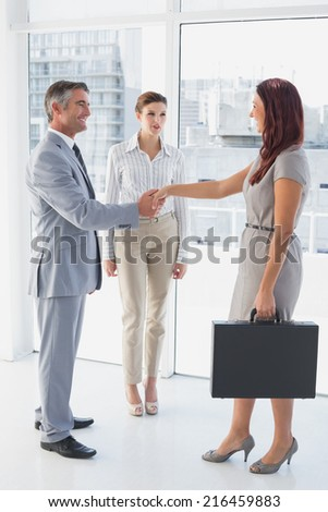 Businessman shaking co-workers hand while at work - stock photo