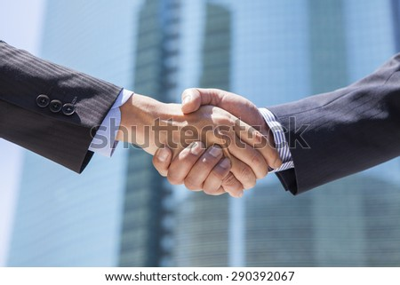 Businessman shaking hands on the street - stock photo