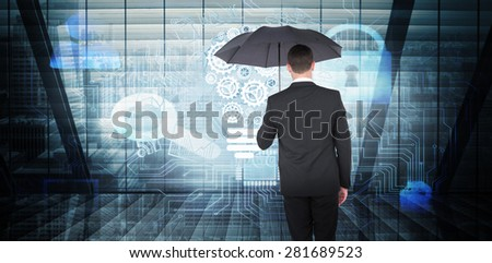 Businessman sheltering under black umbrella against room with large window looking on city - stock photo
