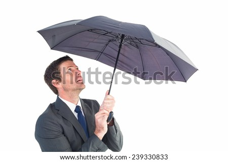 Businessman sheltering under black umbrella on white background - stock photo
