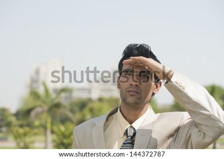 Businessman shielding eyes - stock photo
