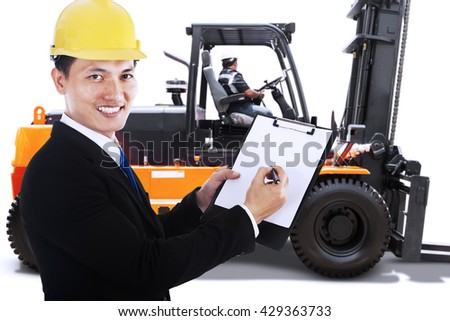 Businessman showing a clipboard while smiling at the camera with a forklift on the background - stock photo