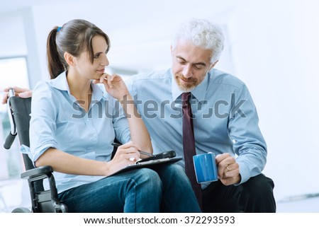 Businessman showing a document on a clipboard to a young woman in wheelchair, assistance and help concept - stock photo