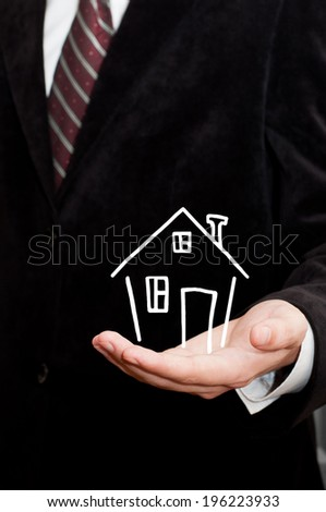 Businessman showing a house in his hand - stock photo