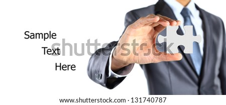 Businessman showing a piece of puzzle. Shot in studio isolated on white - stock photo