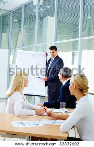 Businessman showing a plan to his colleagues - stock photo