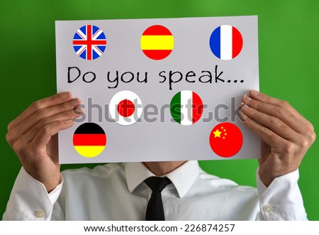 Businessman showing a sheet with text Do you speak and some flags - stock photo