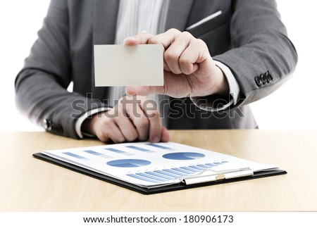 Businessman showing blank business card on table - stock photo