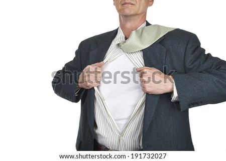 Businessman showing blank superhero suit underneath his shirt standing against city white background - stock photo