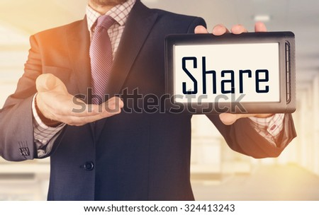 Businessman showing business concept on tablet standing in office - Share - stock photo