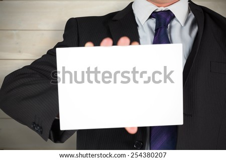 Businessman showing card against bleached wooden planks background - stock photo
