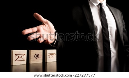Businessman Showing Contact Icons on Small Wooden Pieces on Table. Isolated on Black Background. - stock photo
