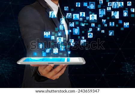businessman showing glow user icon floating from tablet screen - stock photo