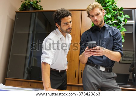 Businessman showing his mobile phone to a colleague - stock photo