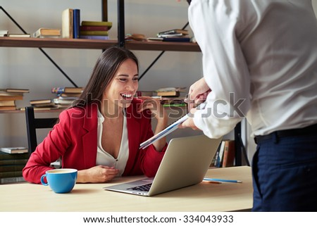 businessman showing his report to smiley businesswoman in office - stock photo