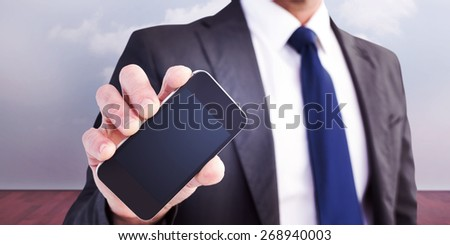 Businessman showing his smartphone screen against clouds in a room - stock photo